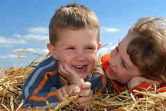 Smiling boy and girl in straw outdoors close-up Stock Photography