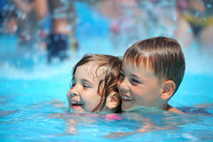 Smiling boy and girl swimming in pool in aquapark. Smiling boy and little girl swimming in pool in aquapark Stock Photo