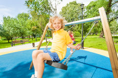 Smiling boy and girl swing in opposite directions Royalty Free Stock Images