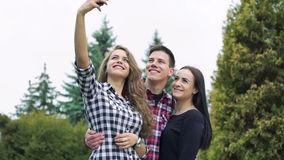 Smiling boy and girls taking a selfie on the green trees background. Slowly stock video