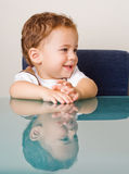 Smiling boy at glass table. Smiling small boy sitting by a glass table Stock Images