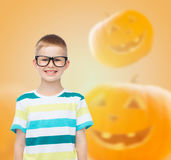 Smiling boy in glasses over pumpkins background Royalty Free Stock Image