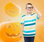 Smiling boy in glasses over pumpkins background Royalty Free Stock Photography