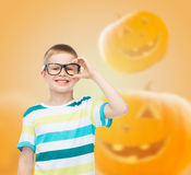 Smiling boy in glasses over pumpkins background Stock Photography