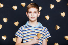 Smiling boy on golden hearts background Stock Photo