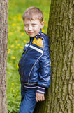 Smiling boy on green background. Standing near tree Stock Photography