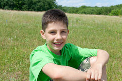 Smiling boy in green outdoors Royalty Free Stock Image