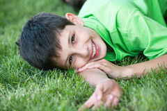 Smiling boy in green on the summer meadow. Happy smiling boy in green is lying on the summer meadow stock photo