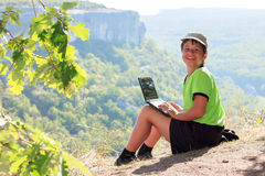 Smiling boy in green t-shirt with a netbook on top of the mounta royalty free stock photography