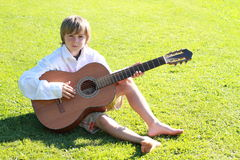 Smiling boy with a guitar. Little boy in white shirt playing a guitar Royalty Free Stock Photos