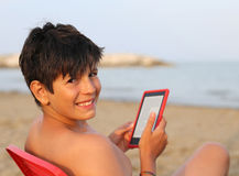 Smiling boy with hair blacks reads an e-book Stock Photography