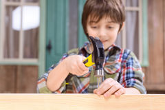 Smiling boy hammering nail in wooden plank Royalty Free Stock Images