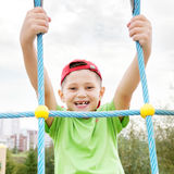 Smiling boy hanging on ropes Stock Photography