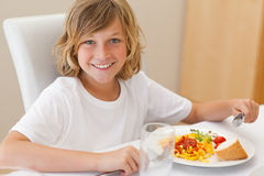 Smiling boy having dinner Stock Photo