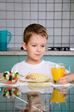 Smiling boy having dinner at the table and takes a glass of oran Royalty Free Stock Photos