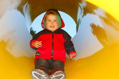 Smiling boy having fun on slide on a playground Royalty Free Stock Photos
