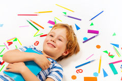 Smiling boy having a rest among heap of stationery Royalty Free Stock Image