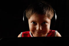 Smiling boy in headphones behind laptop Stock Photos