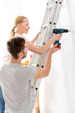 Smiling boy helping girl to keep drill Stock Image