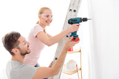 Smiling boy helping girl to keep drill Stock Images
