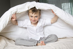 Smiling boy hiding in bed under a white blanket or coverlet. Stock Photography