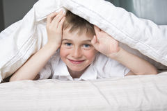 Smiling boy hiding in bed under a white blanket or coverlet. Royalty Free Stock Photos