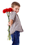 Smiling boy hiding a bouquet. Of red carnations behind itself, isolated on white Royalty Free Stock Photo