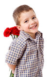 Smiling boy hiding a bouquet. Of red carnations behind itself, isolated on white Royalty Free Stock Images