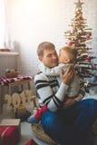Smiling boy and his father near fashion xmas tree Stock Photo