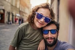 Smiling boy and his father taking selfies outside stock images
