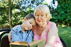 Smiling boy and his grandmother reading a book in the park stock photography