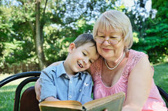 Smiling boy and his grandmother sitting in the park and reading stock photos