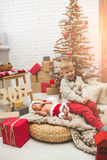 Smiling boy and his little brother near fashion xmas tree Royalty Free Stock Photo