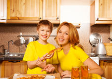 Smiling boy and his mother with pizza in kitchen. Smiling boy holding a slice of pizza and his mother together in the kitchen Royalty Free Stock Photos