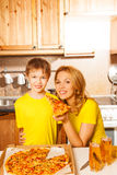 Smiling boy and his mother with pizza slice Stock Photography