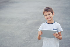 Smiling boy hold tablet computer. School, education, technology, leisure concept Royalty Free Stock Photo