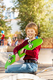 Smiling boy holding with arms green skateboard Royalty Free Stock Images