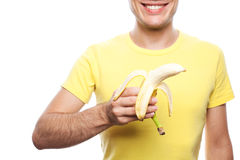 Smiling boy holding banana. Smiling handsome guy holding yellow banana over white background. Healthcare concept. studio shot stock photography