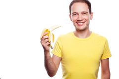 Smiling boy holding banana. Smiling handsome guy holding yellow banana over white background. Copy-space. Healthcare concept. studio shot Royalty Free Stock Photo
