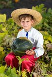 Smiling boy holding  big yellow pumpkin in hands Stock Image