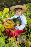 Smiling boy holding  big yellow pumpkin in hands Royalty Free Stock Photography