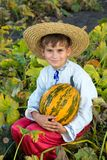 Smiling boy holding  big yellow pumpkin in hands Royalty Free Stock Images