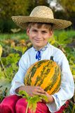 Smiling boy holding  big yellow pumpkin in hands. Little funny boy with pumpkin in national Ukrainian clothes Royalty Free Stock Photo