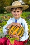 Smiling boy holding  big yellow pumpkin in hands Stock Photo