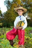 Smiling boy holding  big yellow pumpkin in hands. Little funny boy with pumpkin in national Ukrainian clothes Royalty Free Stock Photos
