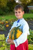 Smiling boy holding  big yellow pumpkin in hands. Little funny boy with pumpkin in national Ukrainian clothes Stock Photo