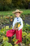 Smiling boy holding  big yellow pumpkin in hands. Little funny boy with pumpkin in national Ukrainian clothes Royalty Free Stock Image