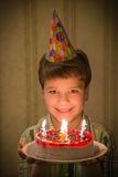 Smiling boy holding birthday cake in hands Royalty Free Stock Image