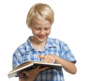 Smiling boy holding book and pointing Royalty Free Stock Image