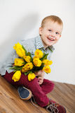 Smiling boy holding a bouquet of yellow tulips in hands sitting on wooden floor. Portrait of smiling boy with a bouquet of yellow tulips flowers in her hands Stock Photography